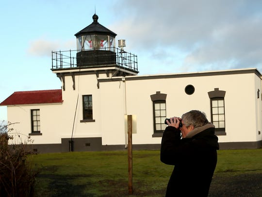 Joe Wright, of Hansville, pauses just past the lighthouse to scope out a few birds with his binoculars while taking part in the Kitsap Audubon Christmas Bird Count at Point No Point on Saturday.