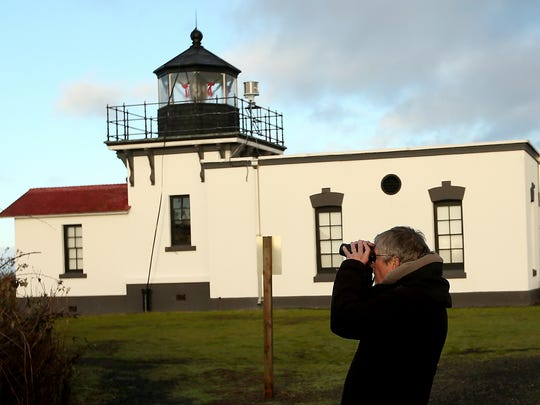 Joe Wright, of Hansville, pauses just past the lighthouse to scope out a few birds with his binoculars while taking part in the Kitsap Audubon Christmas Bird Count at Point No Point on Saturday, Dec. 30, 2017.