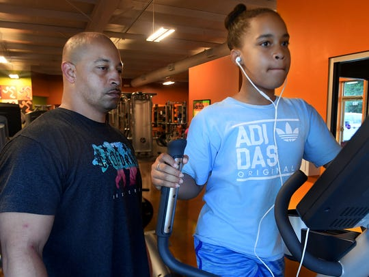 Rodney Stephenson makes sure his youngest daughter, Melony is squared away as she utilizes the elliptical machine during a morning workout, Tuesday, June 12. Melony, 11, says she enjoys going to the gym with her father because of the time he gets to spend with them.