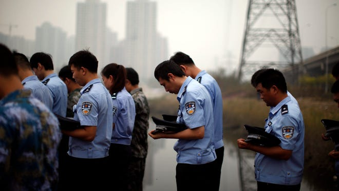 Soldiers, policemen and paramilitary policemen attend a mourning service for the victims in the August 12 chemical explosions at the blast site in Tianjin, China, August 18, 2015.