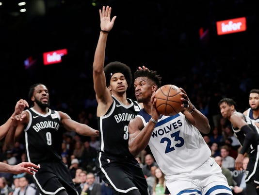 Minnesota Timberwolves' Jimmy Butler (23) looks to pass away from Brooklyn Nets' Jarrett Allen (31) and DeMarre Carroll (9) during the first half of an NBA basketball game Wednesday, Jan. 3, 2018, in New York. (AP Photo/Frank Franklin II)