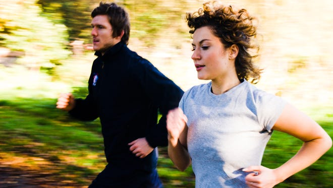 Runners train in a park.