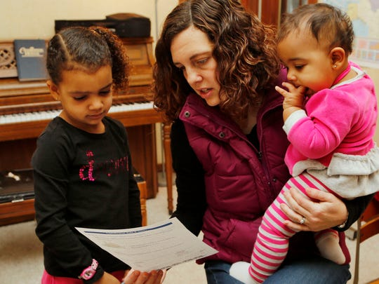 Carlee Dawodu holds her nine-month-old daughter Eden as she check the English lesson of daughter Keziah, 6, Wednesday, December 17, 2014, in their Lafayette home. With a gap in he ages of all four of her daughters, Dawodu prefers homeschooling as a way to keep the children together.