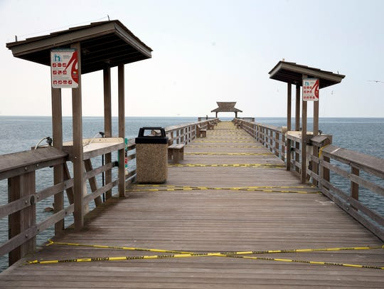 Caution tape lines the second half of the Naples Pier,