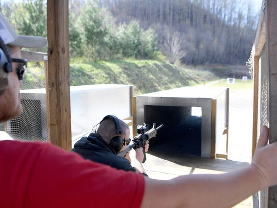 Aaron Jones, a range officer, watches as Javier Moraga fires an AR-15 at the Wayne E. Smith Cold Mountain Shooting Range in Haywood County on Friday, April 27, 2018.