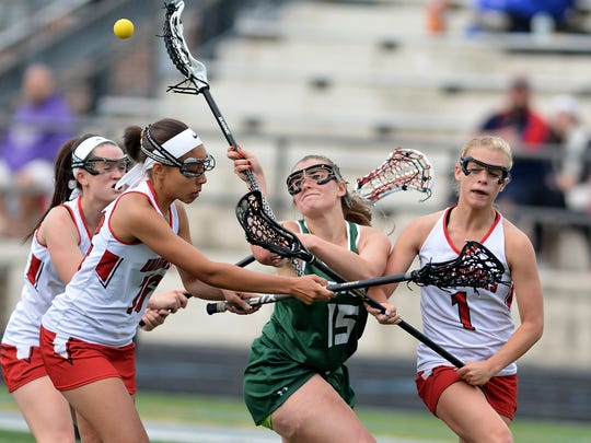 York Catholic's Sarah Mazzur battles for the ball with a host of Susquehannock defenders during the York-Adams girls' lacrosse semifinals at Dallastown High School, Wednesday May 10, 2017. John A. Pavoncello photo