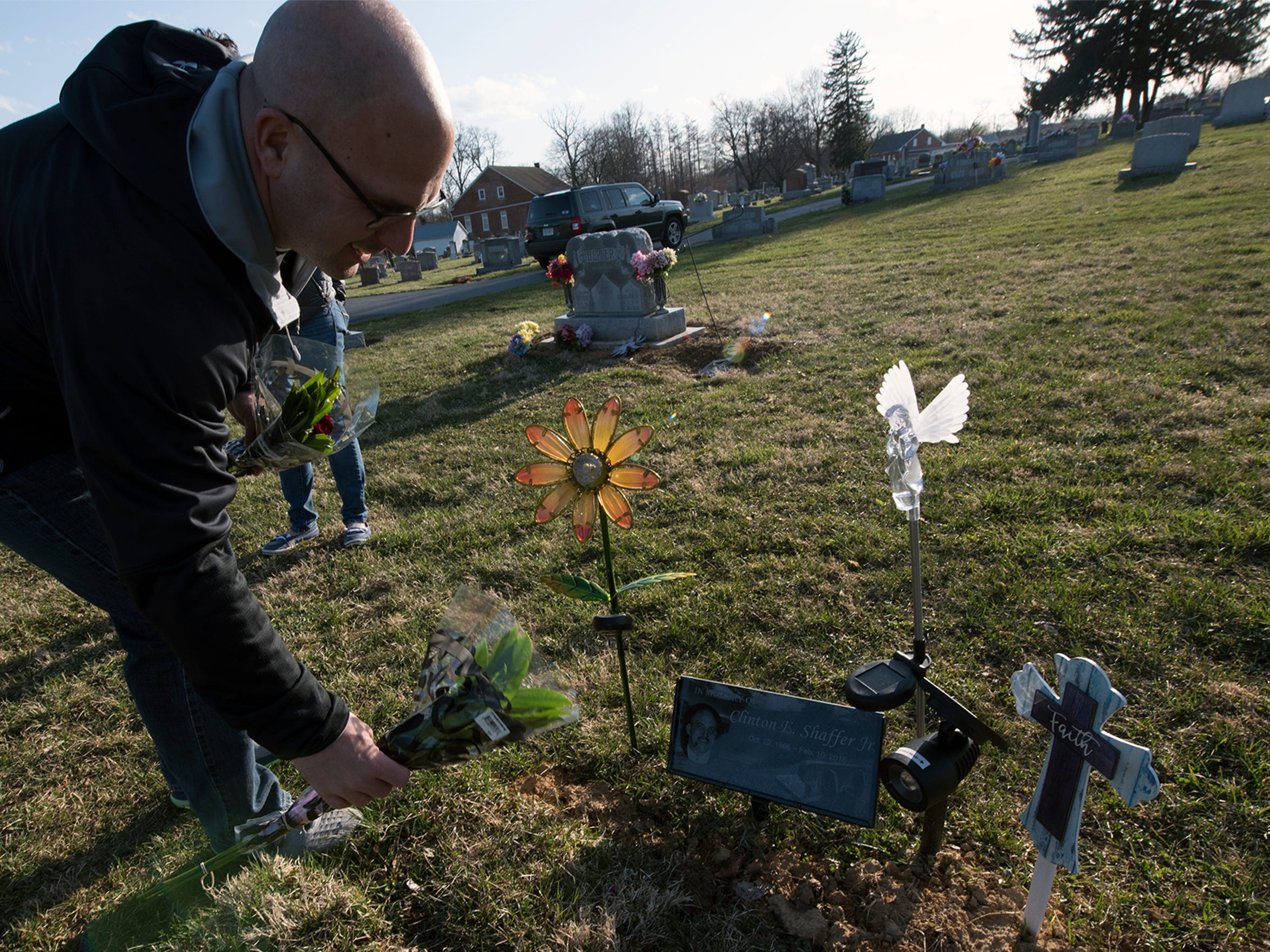 John Barton puts a rose on his brother's gravesite on Thursday at Trinity Fellowship Church cemetery in Waynesboro.