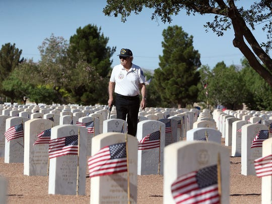 Korean War veteran Pete G. Flores looks for the grave marker of his son, David Flores, who died in Vietnam at the age of 20 during Memorial Day observances at Fort Bliss National Cemetery.
