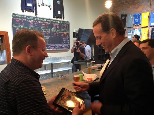 "Former U.S. Sen. Rick Santorum signs a copy of his book, ""It Takes a Family,"" for Chris Taylor, a native of Shell Rock, Ia., who now lives in Washington, D.C."