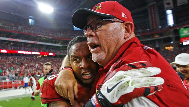 Arizona Cardinals head coach Bruce Arians greets Rashad Johnson after he broke up a pass in the end zone to secure their 24-20 win against the Philadelphia Eagles on Oct. 26, 2014 in Glendale.