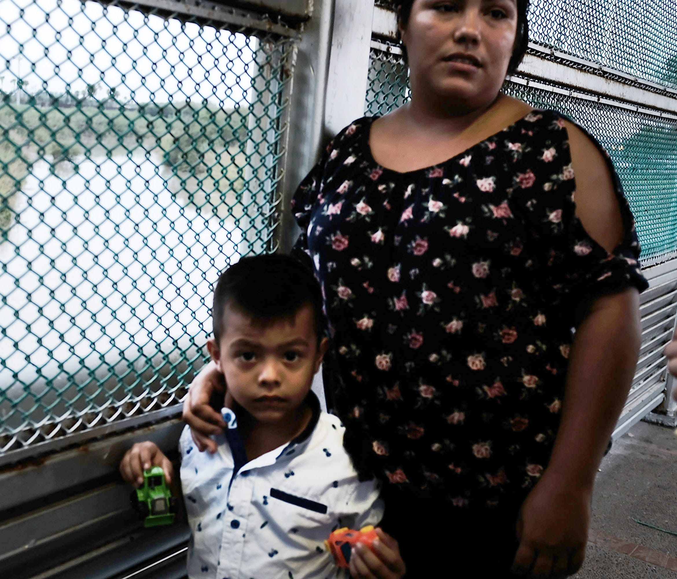 A Mexican woman and her child are held up by the border patrol as they try to enter into Brownsville on June 21, 2018 in Brownsville, Texas.
