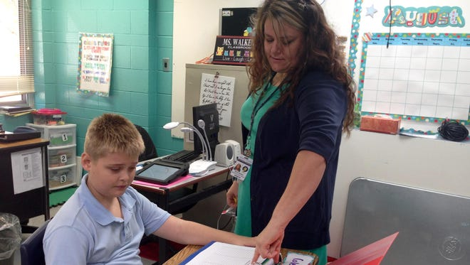 South Grant Elementary teacher Shira Walker talks with Cole Davis, 9, about his mock bank account on the first day of school Friday. Davis will practice adding, subtraction and organization with the Minion Money Shack classroom bank.