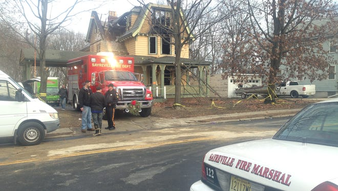 Sayreville fire officials are pictured on Monday at the Main Street home of the DeSarno-Klitzke family, whose church, Holy Trinity Episcopal in South River, is collecting monetary donations to help them rebuild their lives.