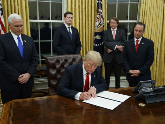 President Donald Trump, flanked by Vice President Mike