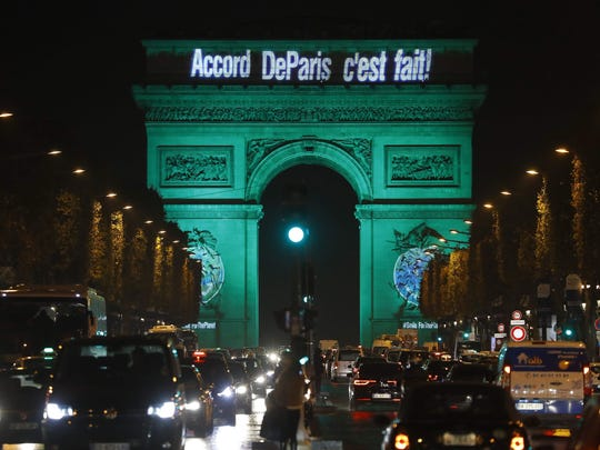 This file photo taken on November 04, 2016 shows The Arc de Triomphe (Arch of Triumph) illuminated with the lettering reading 'The Paris accord is done' in Paris, to celebrate the first day of the application of the Paris COP21 climate accord.