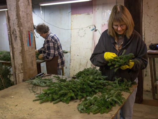 Marianne Gatton assembles wreaths in the barn at Wade