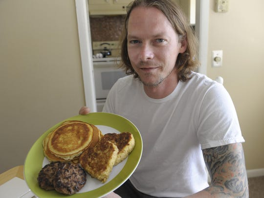 Owner/Chef Matt Dalton holds a plate of pancakes, French toast and sausage that he doesn't get to cook at his Detroit restaurant.