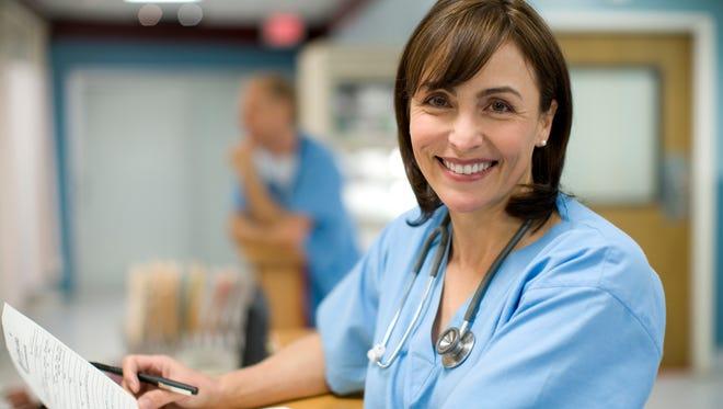 A hospital nurse looks over paperwork.