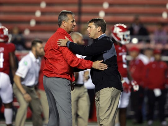 Ohio State head coach Urban Meyer, left, greets Rutgers