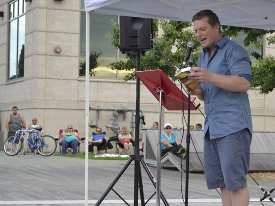 Jacob Schwahn reads a Bible passage during the Worship on the Water service on the CityDeck in downtown Green Bay on Sunday night, July 10, 2016. Schwahn, who does local ministry, is the facilitator of the Pray, Green Bay online network.