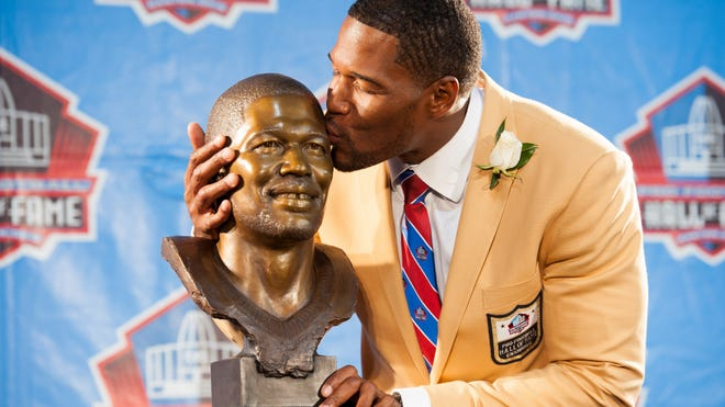 Former New York Giants defensive end Michael Strahan with his bust during the 2014 Pro Football Hall of Fame Enshrinement at Fawcett Stadium, Aug. 2, 2014. (Photo by Jason Miller/Getty Images)