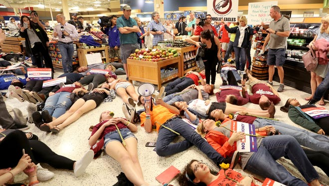 "Demonstrators lie on the floor at a Publix Supermarket in Coral Springs, Fla., Friday, May 25, 2018. Students from the Florida high school where 17 people were shot and killed earlier this year did a ""die in"" protest at the supermarket chain that backs a gubernatorial candidate allied with the National Rifle Association. Shortly before the the ""die-in"" Publix announced that is will suspend political donations. (Mike Stocker/South Florida Sun-Sentinel via AP)"