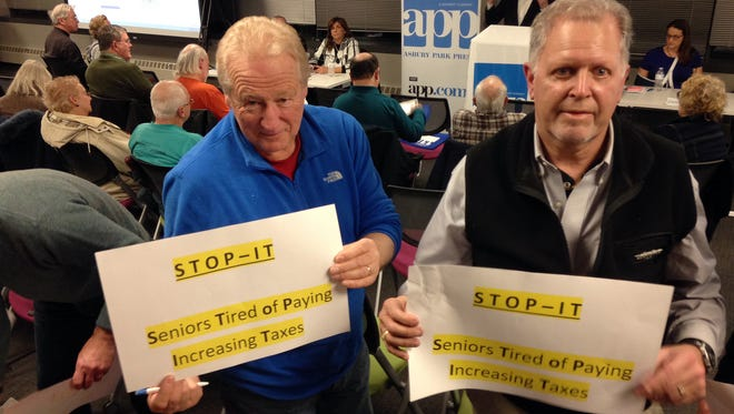 Jim Salerno (left) and Carl N. Steinberg, both Ocean Towsnhip, hold up signs at the end of the Taxed Out Appeal session at the Asbury Park Press in Neptune Tuesday, January 5, 2016.