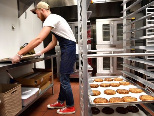 Kitchen manager Nick Nedved puts more cookies in the
