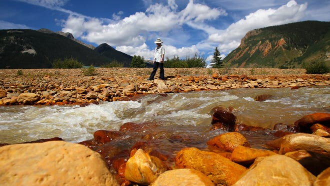 Melanie Bergolc, a resident of Silverton, Colo., walks along the banks of Cement Creek in Silverton on Aug. 10, 2015, where residue from the Gold King Mine spill is evident.