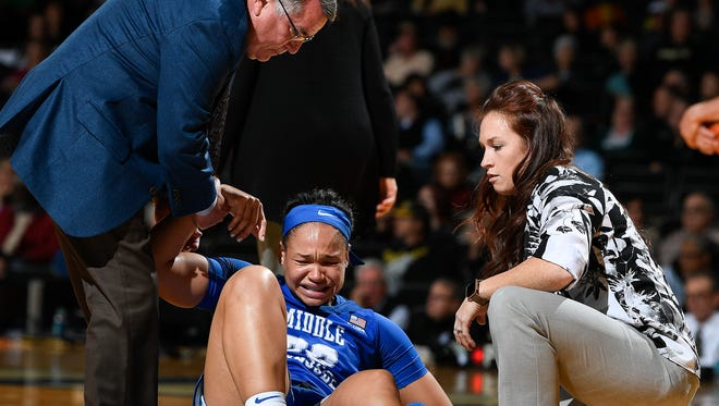MTSU coach Rick Insell helps forward Alex Johnson (00) off the floor after she was injured during the first half against Vanderbilt on Nov. 10.