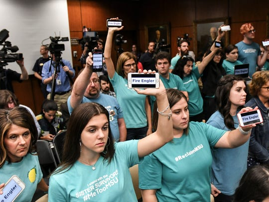 Victims of Larry Nassar, along with friends, family, and other supporters call on the MSU Board of Trustees to fire interim President John Engler, Friday, June 22, 2018, during the first MSU Board of Trustees meeting since the $500 million settlement stemming from the Larry Nassar scandal.  [AP Photo/Matthew Dae Smith/Lansing State Journal]