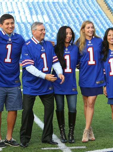 Terry Pegula, center, new owner of the Buffalo Bills, braces to catch a tossed football as he poses with his family inside Ralph Wilson Stadium. From left are his daughter Jessica, son Matthew, Terry, daughter's Kelly, Laura and wife Kim.