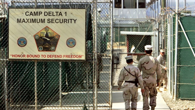 "In this June 27, 2006 file photo, reviewed by a U.S. Department of Defense official, U.S. military guards walk within Camp Delta military-run prison, at the Guantanamo Bay U.S. Naval Base, Cuba. A draft executive order shows President Donald Trump asking for a review of America's methods for interrogation terror suspects and whether the U.S. should reopen CIA-run ""black site"" prisons outside the U.S."