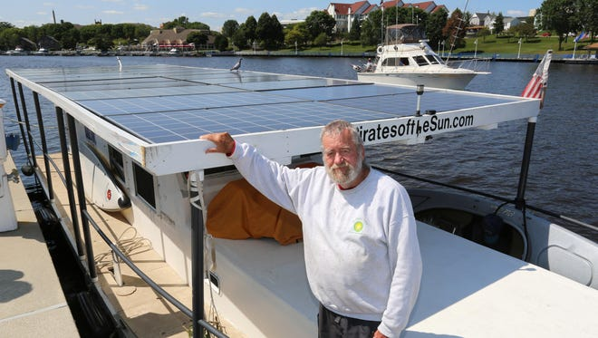 """Jim Greer, captain of the solar-powered boat """"RA"""" poses at the front of his boat during a stop at the Sheboygan riverfront Friday, August 25, 2017, in Sheboygan, Wis."""