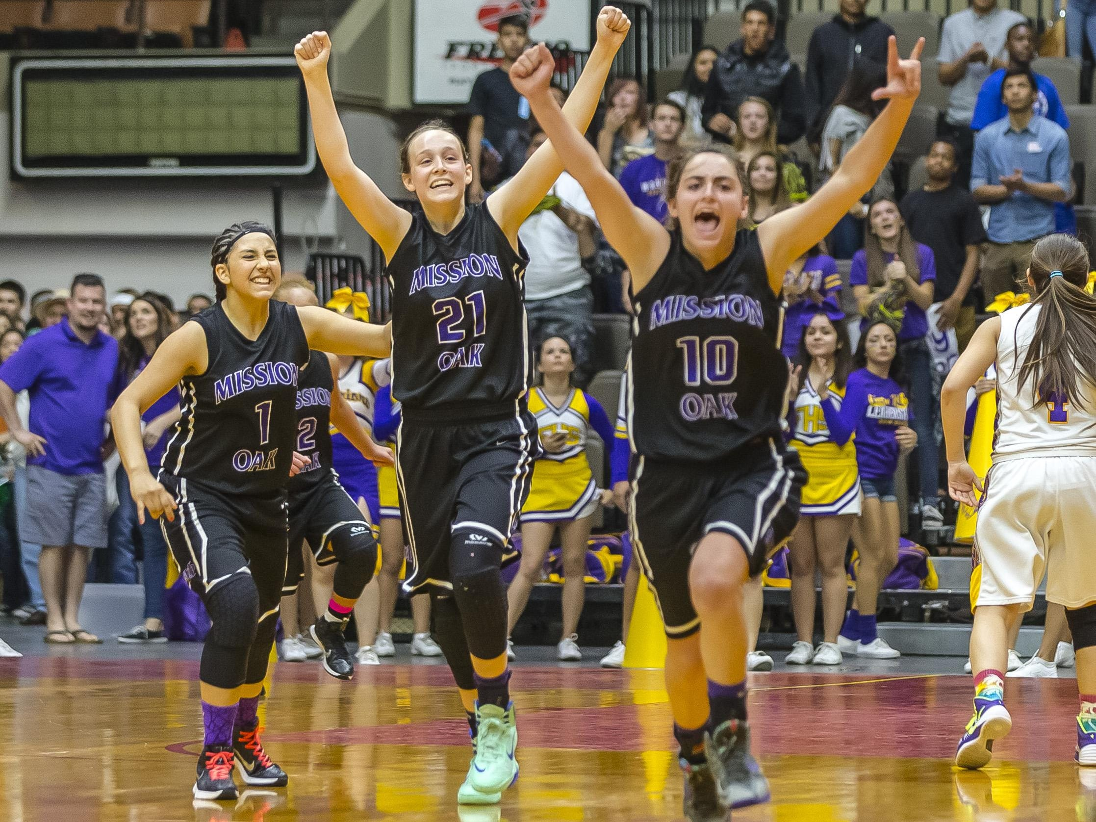 Mission Oak's Tristen Myers (21) Rhegan Fernandes (10) and Samantha Ruvalcaba (1) celebrate winning the 2014-15 Central Section Division III championship at Selland Arena in Fresno.