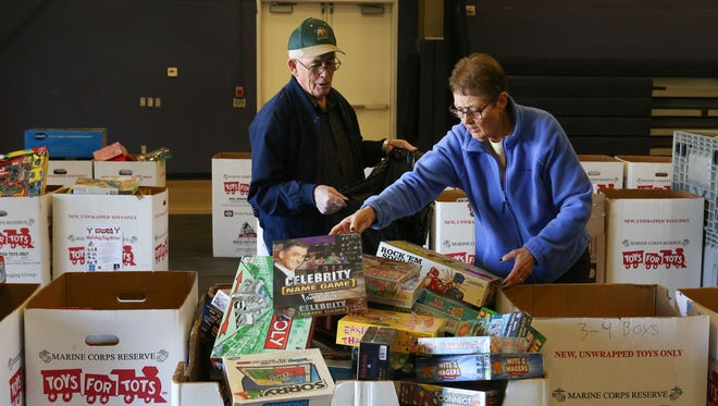 Volunteers with the Desert Chapel Church, Pat and Chuck Johnson pick out toys for a child during the Toys for Tots distribution in Palm Springs.