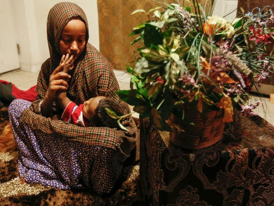 Somali refugee Mun Omer holds her one-year-old son