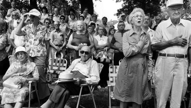 """Maude Ballard, left, Harrison Toon, and Mr. and Mrs. Ray Pharris lisstened to """"The Star-Spangled Banner"""" yesterday as the Fancy Farm Picnic officially opened for the 101st time. Photo published Aug 2, 1981. PUBLICATION PROHIBITED Authority to publish or copy MUST be obtained from Courier-Journal management. To obtain permission call 502-582-4601. 525 W. Broadway, Louisville, KY 40201."""
