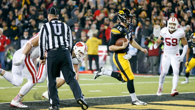 Iowa's Jake Rudock runs for a touchdown against Wisconsin on Saturday. The junior from Weston, Fla., now has 4,557 passing yards, moving him past Kyle McCann and into eighth on Iowa's career list.