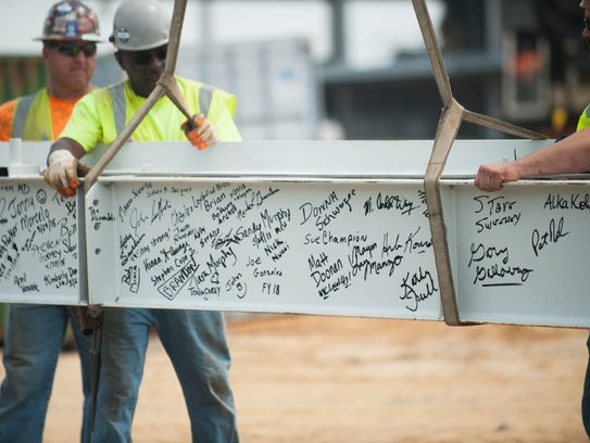 Workers prepare to raise a signed steel beam during