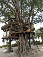 Lynn Tran and her husband Richard Hazen pose in their Australian pine treehouse Thursday, Jan. 4, 2018, in Holmes Beach, Fla. The couple is hoping the U.S. Supreme Court will hear their case after city and state officials ordered the treehouse removed.