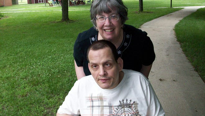 Linda Scherer takes her brother, Holly Center resident David Douglas, for a stroll on the grounds of Holly Center.