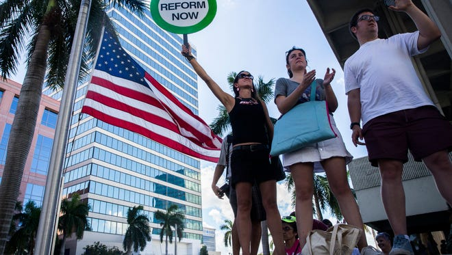 Alessandra Mondolfi, center, listens to speeches during a gun control rally in front of the federal courthouse in Fort Lauderdale, Fla. on Saturday, Feb. 17, 2018.