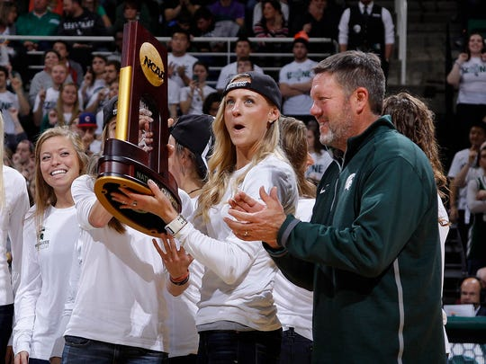 Leah O'Connor holds the trophy as coach Walt Drenth, right, stands by as the national championship Michigan State cross country team is honored during a timeout against Santa Clara Monday, Nov. 24, 2014, in East Lansing, Mich.