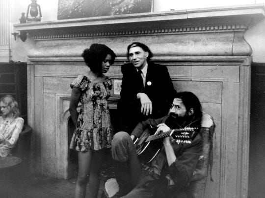 Guitarist Peter Walker, right, plays a tune as civil rights attorney William Kuntsler chats with an unidentified woman at the Gar Wood mansion.
