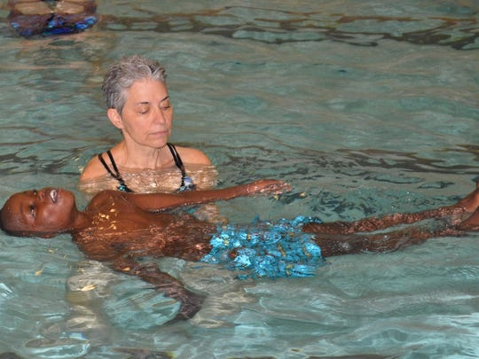 Janvier Mbilizi perfects his back float with the help of his teacher Lynda Siegel at the Greater Burlington YMCA pool.