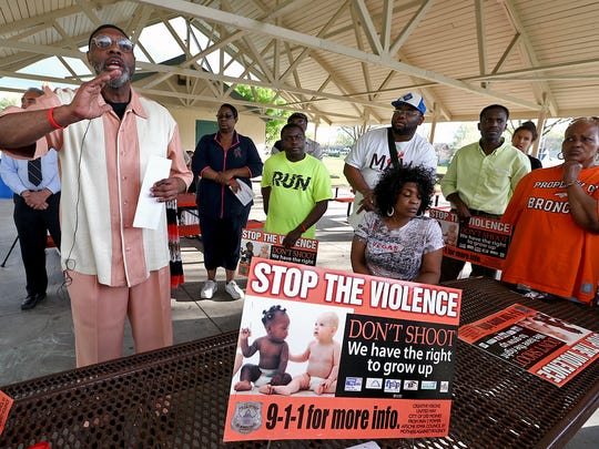 """Ako Abdul-Samad, left, director of Creative Visions, addresses the crowd at a """" Stop the Violence """" prayer vigil and gathering held at Evelyn Davis Park in Des Moines on Thursday evening May 8, 2014."""