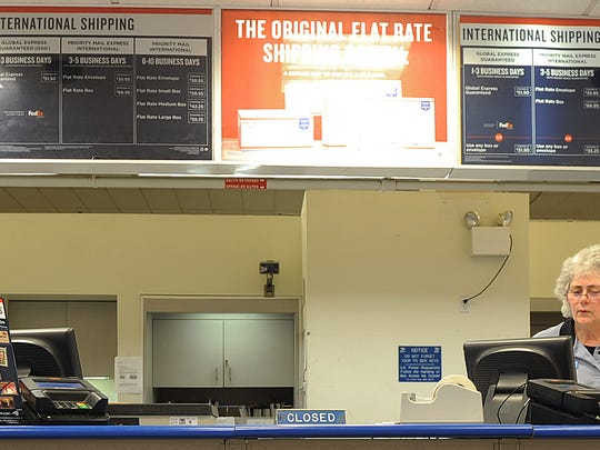 Gail Handley and Connie AU work the counter at Mansfield Post Office main office on Diamond Street.