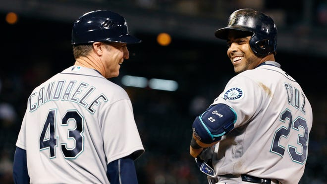Seattle Mariners' Nelson Cruz, right, and first base coach Casey Candaele smile after Cruz hit a single during the sixth inning of a baseball game against the Chicago White Sox in Chicago, Thursday, Aug. 25, 2016.