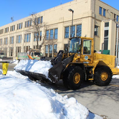 A Green Bay public works crew clears snow Thursday